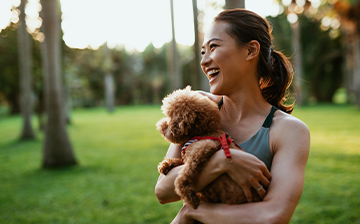 Woman holding small dog laughing