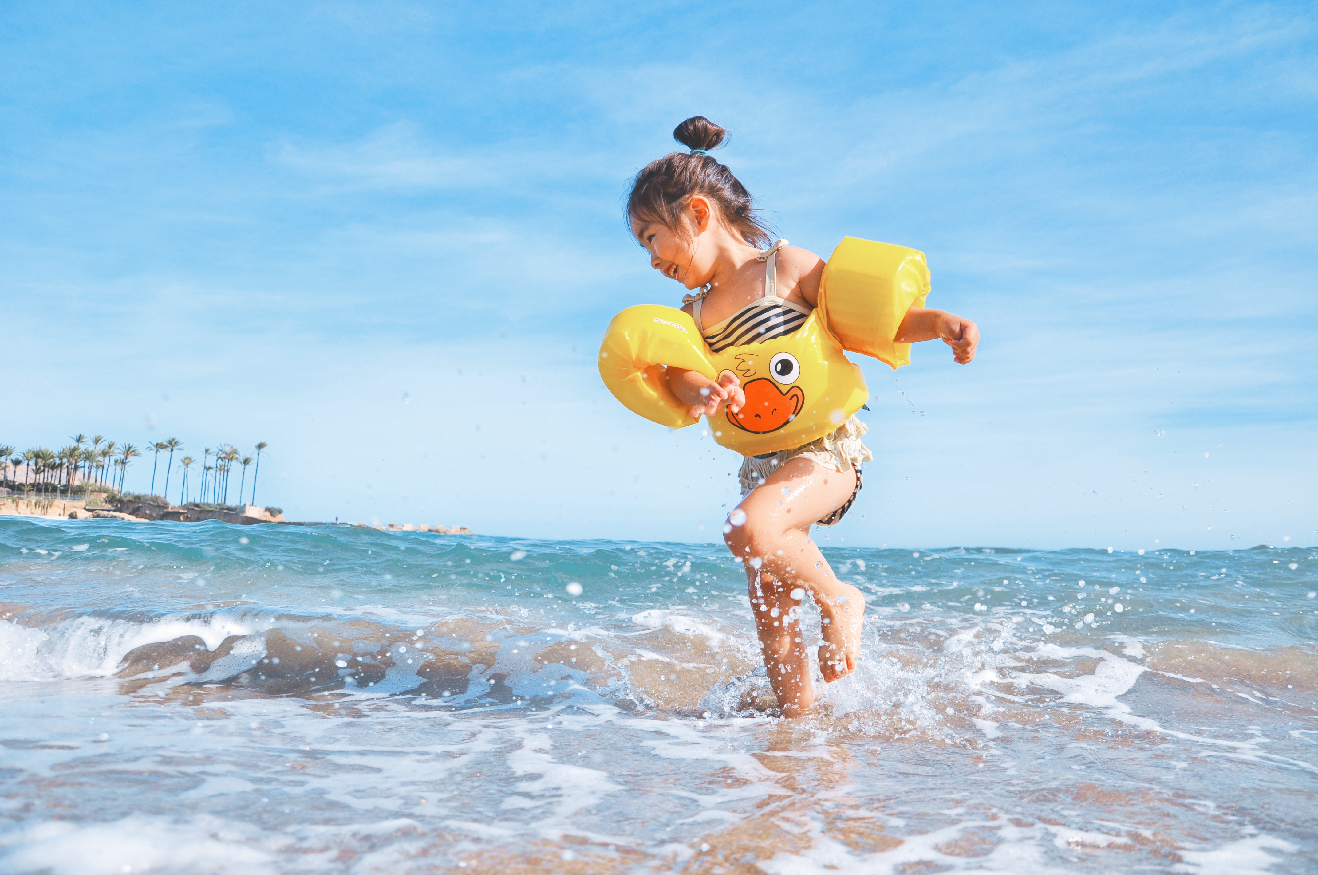 Girl wearing duck float on the beach