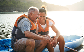 Older father and adult daughter in a boat on a lake