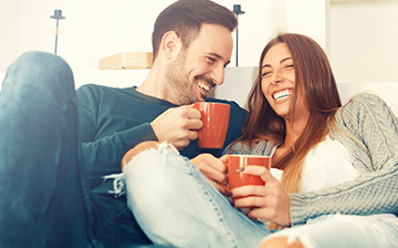 Man and woman drinking coffee while relaxing on a sofa
