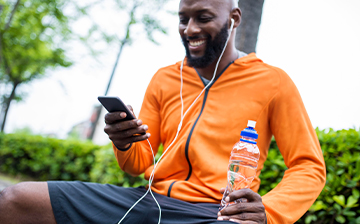Man listening to music and holding a water bottle and a phone