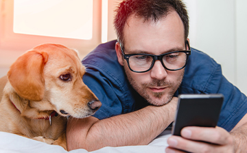 Man updating card info on cellphone with dog next to him