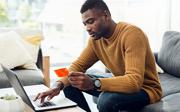 Man paying with credit card on laptop